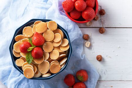tiny pancakes cereals with strawberries in blue bowl on blue gauze on white background, top view, trendy food Banque d'images