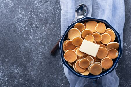 top view tiny cereal pancakes with butter in blue bowl, spoon on blue gauze on grey background, trendy food concept, copy space