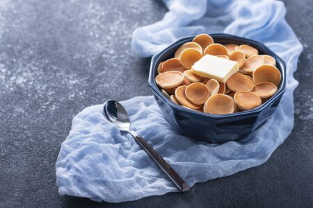 tiny cereal pancakes with butter in blue bowl, spoon on blue gauze on grey background, trendy food, copy space Banque d'images