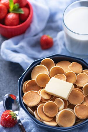 closeup tiny cereal pancakes with slice of butter, strawberries, glass of milk on blue background, rural Breakfast concept, vertical