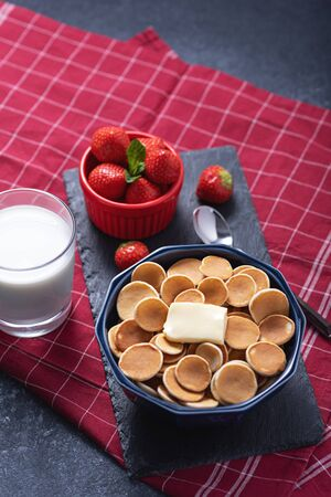 trendy tiny cereal pancakes with slice of butter in blue bowl, strawberries, glass of milk on red background, rural Breakfast concept, vertical, top view Stock Photo