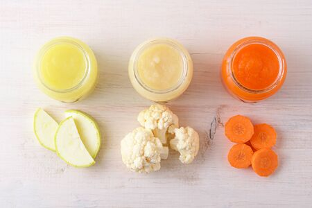 top view children's vegetable food on white background, natural homemade mashed zucchini cauliflower, carrots Stock Photo