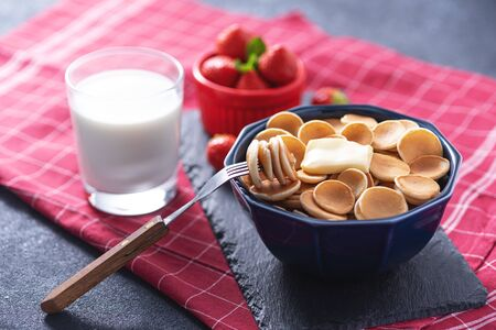 tiny cereal pancakes in blue bowl with strawberries, glass of milk on red cloth napkin, rustic Breakfast concept Banque d'images