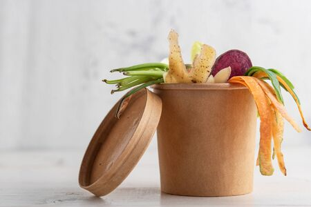 vegetable peels in composting pot on white background, closeup Stock Photo