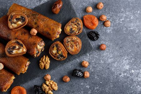dried apricots, prunes, nuts in Apple roll on gray background, Oriental desserts concept, top view Banque d'images