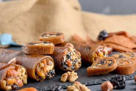closeup dried apricots, prunes, nuts in Apple roll on gray background, Oriental desserts concept, healthy vegetarian snack