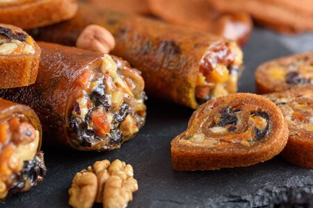 healthy vegetarian snack, roll up with prunes, dried apricots, nuts and honey on black background