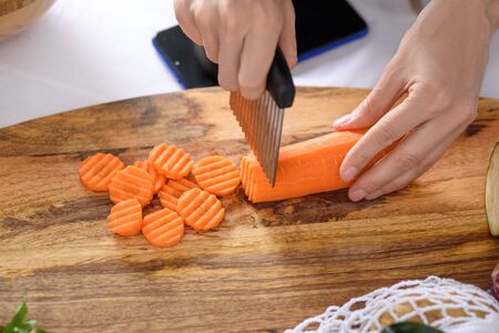 women's hands cut carrots with curly wavy knife on wooden Board, quilling, closeup Banque d'images