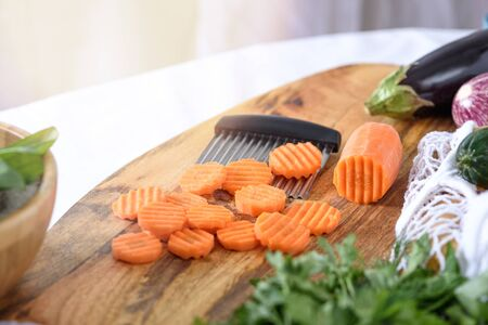 carrots slice with curly wavy knife on wooden Board, quilling, vegetables Banque d'images - 150098392