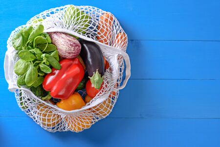 pepper, eggplant, spinach, tomatoes, carrots in white string bag, vegetable bag on blue background, summer harvest concept, copy space, top view
