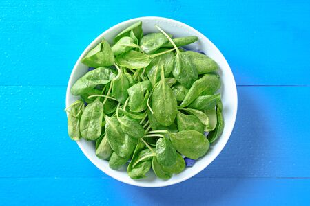 spinach with drops in bowl on blue background, harvest, top view, Banque d'images