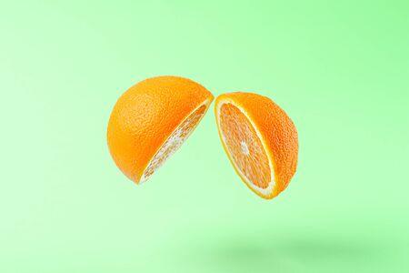 creative sliced orange on green background with levitation effect