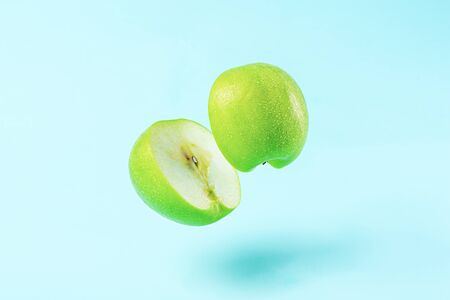 sliced Apple on blue background with levitation effect, minimal concept Stock Photo