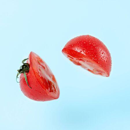 sliced tomato on blue background with levitation effect, art vegetable