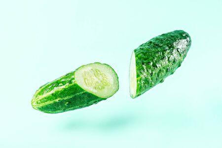 sliced cucumber on blue background with levitation effect, art vegetable concept
