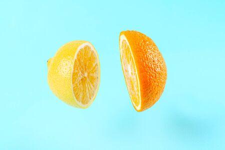 sliced lemon orange on blue background with levitation effect, art fruit minimal concept