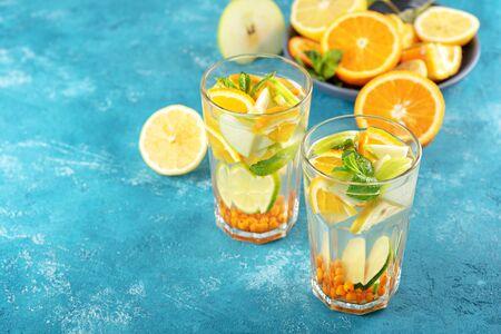 summer refreshing lemonade with orange, lemon, mint in glasses on blue background
