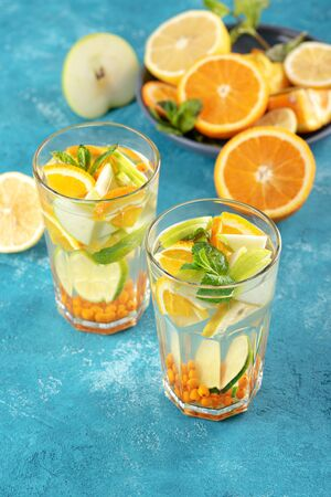 summer homemade refreshing lemonade with orange, lemon, mint in glasses on blue background, vertical