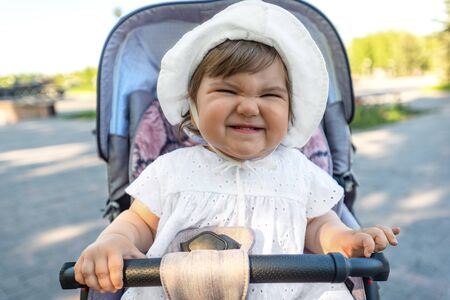 portrait of funny smiling baby girl in white hat sitting in stroller, make faces, happy childhood concept Stock Photo