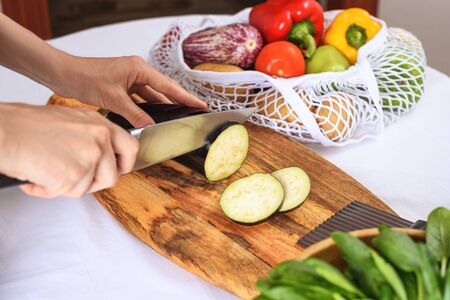 slicing eggplant on wooden Board with knife, cooking vegetarian dinner, closeup