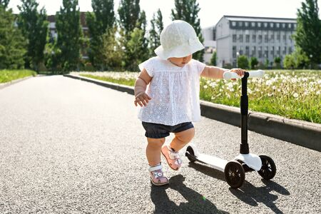 baby girl with scooter in Park, child in white hat learn to ride, active summer Stock Photo