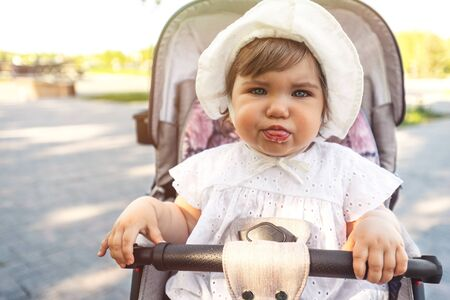 portrait of funny baby girl in white hat sitting in stroller, make faces