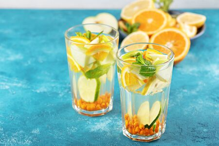 summer cocktail with orange, lemon, mint in glasses on blue background, closeup