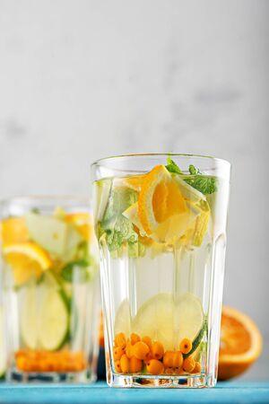 summer refreshing lemonade with orange, lemon, mint in glasses on white background, lemon water concept Stock Photo