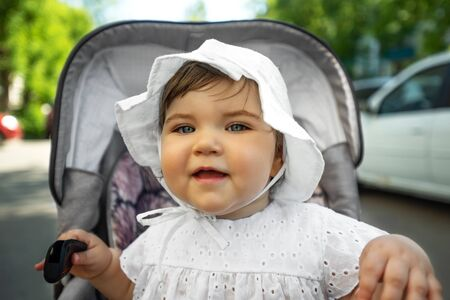 portrait of baby girl in white hat sitting in stroller, closeup Banque d'images - 149476223