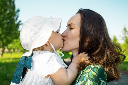 mom and daughter kissing, unconditional love, happy motherhood, childhood summertime