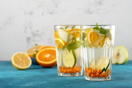 closeup orange water with sea buckthorn and mint in glasses on white blue background, summmer drink concept