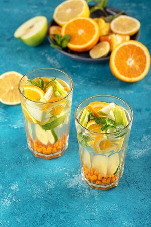 vertical homemade lemonade with lemon, orange, sea buckthorn and mint in glasses on blue background, summer drinks concept