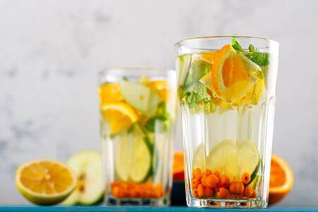 homemade lemonade with lemon, orange, sea buckthorn and mint in glasses on white background, summer drinks concept