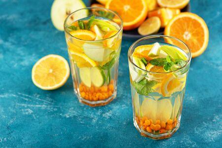 refreshing detox water with lemon, orange, mint in glasses on blue background, summer lemonade concept