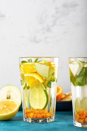 refreshing detox water with lemon, orange, mint in glasses on white blue background, summer homemade lemonade concept, vertical