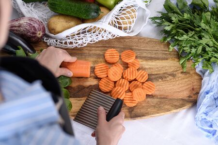 process of slicing carrots with wavy fluted knife, quilling, vegetables in string bag, top view Banque d'images - 148985900
