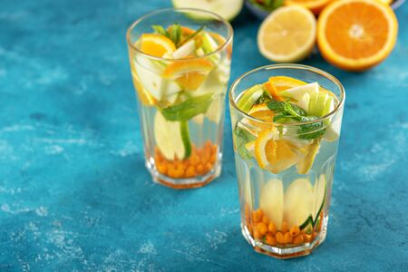 homemade lemonade with lemon, orange, sea buckthorn and mint in glasses on blue background, summer drink concept Stock Photo