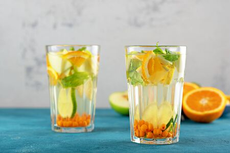 orange water with sea buckthorn and mint in glasses on blue background, summmer drinks concept Stock Photo