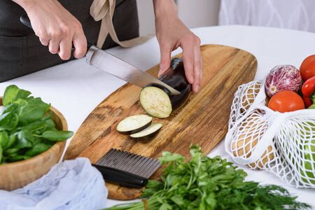 women's hands cut eggplant with knife on wooden Board, the process of cooking moussaka, cooking at home Banque d'images