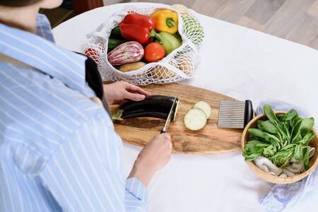process of slicing eggplants for moussaka on wooden Board, cooking at home concept, vegetables in string bag