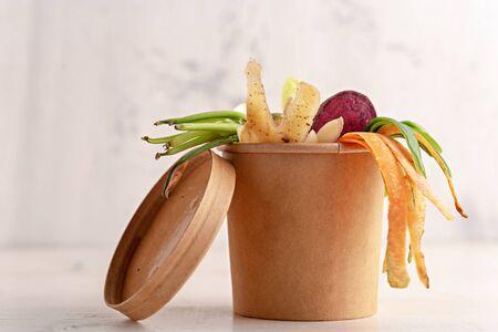 vegetable peels in cardboard pot on white background, composting concept, food waste, eco life Banque d'images