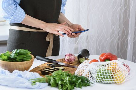 women's hands with smartphone in kitchen, cooking vegetables, cooking at home concept Stock Photo