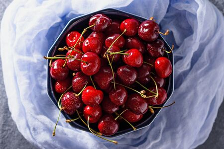 top view cherries with drop in blue bowl on blue gauze, closeup Stock Photo