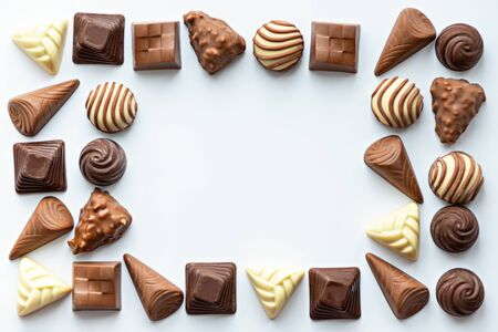 chocolate candies frame on white background, copy space, top view, space for text, world chocolate day concept Stock Photo
