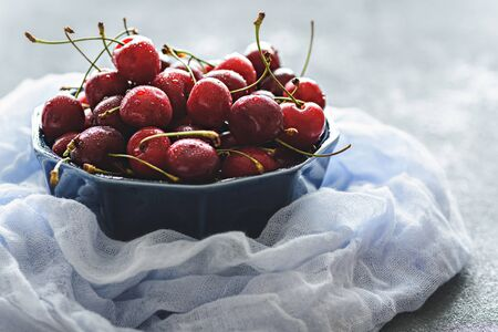 cherries with drop in blue bowl on blue gauze, closeup