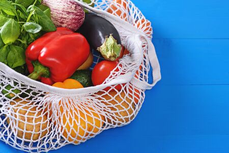 vegetables in white string bag, crops on blue background, natural organic food, copy space, eco products