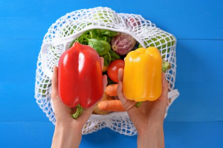 red and yellow peppers in hands over bag of string bags with vegetables on blue background, eco-friendly organic products concept, top view