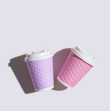 two colored paper cups on white background with shadow, top view