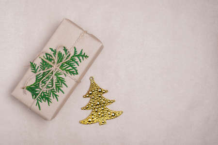 gift craft box with branch of thuja on craft background, gold toy tree, new year's composition, copy space, top view, DIY, me-gift