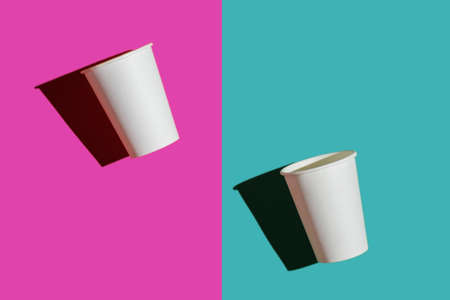 two white paper biodegradable cups on colored backgrounds, top view, mock up